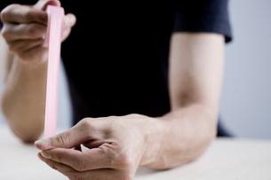 ビニールテープを引く男性の手元の写真素材 [FYI04066765]