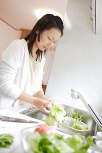 キッチンで野菜を洗う女性の写真素材 [FYI04066833]
