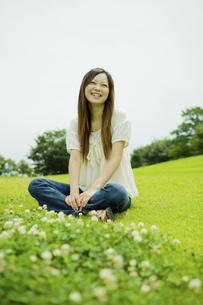 公園の芝生にあぐらを組んで座る20代女性の写真素材 [FYI04066868]