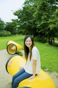 公園の黄色いオブジェに腰掛ける20代女性の写真素材 [FYI04066875]