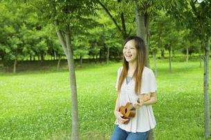公園の木陰でウクレレを弾く20代女性の写真素材 [FYI04066880]
