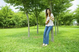 公園の木陰でウクレレを弾く20代女性の写真素材 [FYI04066882]