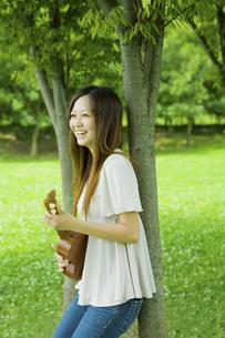 公園の木陰でウクレレを弾く20代女性の写真素材 [FYI04066883]