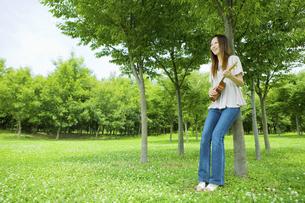 公園の木陰でウクレレを弾く20代女性の写真素材 [FYI04066886]