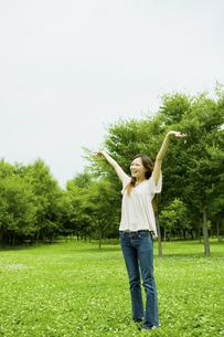 公園の芝生に立って伸びをする20代女性の写真素材 [FYI04066890]