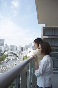 ベランダから市内を眺めるカップルの写真素材 [FYI04067346]