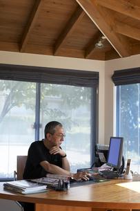 書斎でパソコンを見る男性の写真素材 [FYI04067362]