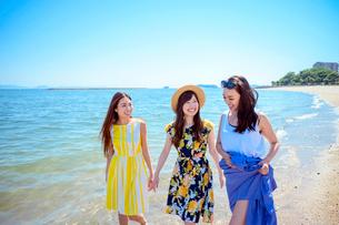 海岸で遊ぶ海のリゾートへ旅する女性3人の写真素材 [FYI04067487]