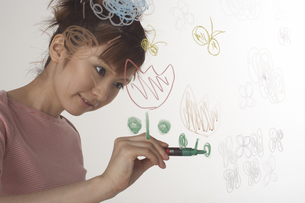 ガラスに絵を描く女性の写真素材 [FYI04067513]