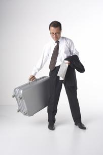 スーツケースを持っているスーツを着た男性の写真素材 [FYI04067514]