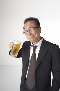生ビールを飲んでいるスーツを着た男性の写真素材 [FYI04067516]