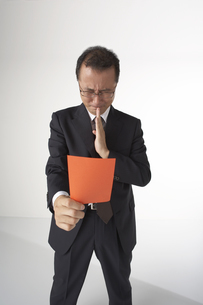 レッドカードを拝んでいるスーツを着た男性の写真素材 [FYI04067519]