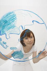 ガラスに地球の絵を描く女性の写真素材 [FYI04067527]