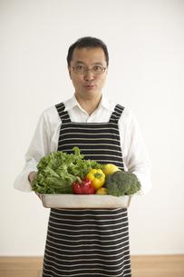 エプロンをして野菜を持っている男性の写真素材 [FYI04067566]