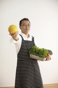 エプロンをして野菜を持っている男性の写真素材 [FYI04067575]