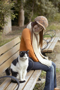 公園のベンチに座っている女性と猫の写真素材 [FYI04067593]