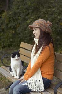 公園のベンチに座っている女性と猫の写真素材 [FYI04067594]