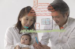 家の絵を描く夫婦と赤ちゃんの写真素材 [FYI04067604]