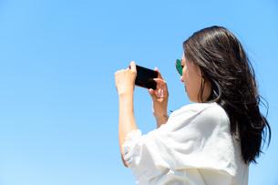スマホで写真を撮る海のリゾートへ旅する女性の写真素材 [FYI04067651]