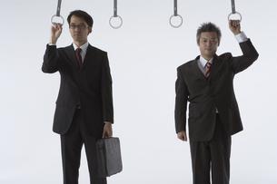吊革につかまっている二人のビジネスマンの写真素材 [FYI04067664]
