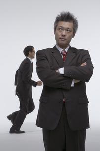 腕組みをしたビジネスマンと走っているビジネスマンの写真素材 [FYI04067666]