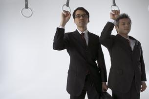 吊革につかまっている二人のビジネスマンの写真素材 [FYI04067667]