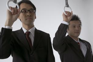 吊革につかまっている二人のビジネスマンの写真素材 [FYI04067673]