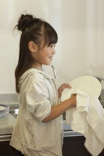お皿を拭いている女の子の写真素材 [FYI04067698]