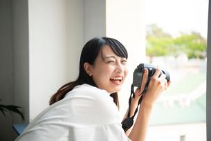 一眼レフカメラを構えて笑っている女性の写真素材 [FYI04067712]
