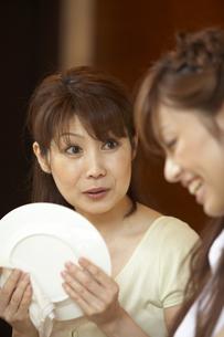 キッチンで皿を拭きながら会話をする母と娘の写真素材 [FYI04067718]