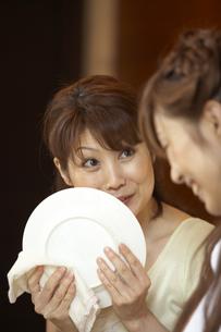 キッチンで皿を拭きながら会話をする母と娘の写真素材 [FYI04067721]