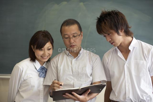 黒板の前に立つ先生と生徒の写真素材 [FYI04067734]
