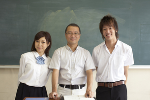 黒板の前に笑顔で立つ先生と生徒の写真素材 [FYI04067738]