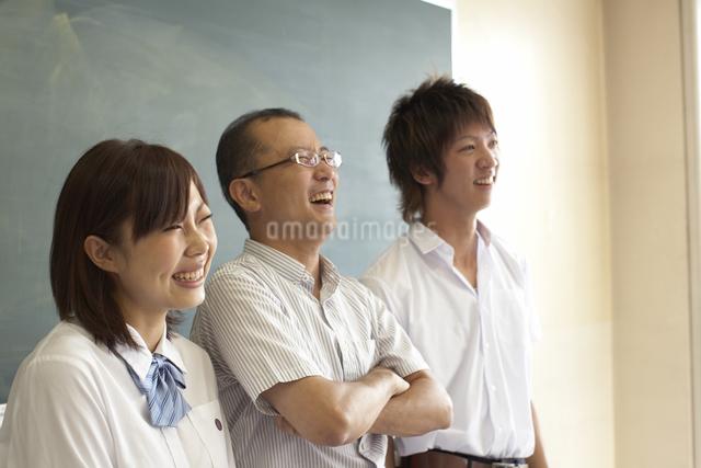 黒板の前に立つ先生と生徒の写真素材 [FYI04067741]