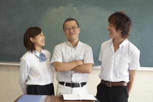 黒板の前に笑顔で立つ先生と生徒の写真素材 [FYI04067742]
