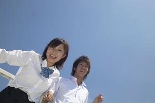 屋上で青空をバックにはしゃぐ男子学生と女子学生の写真素材 [FYI04067745]