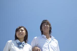 屋上で青空をバックに笑う男子学生と女子学生の写真素材 [FYI04067749]