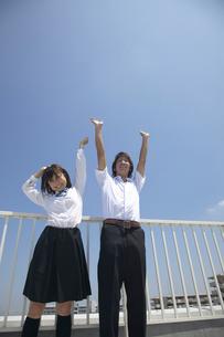 屋上で青空をバックに背伸びする男子学生と女子学生の写真素材 [FYI04067754]