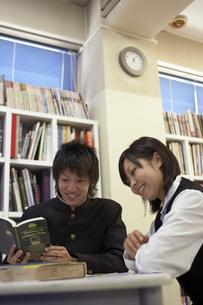 図書室で本を読む男子学生と女子学生の写真素材 [FYI04067759]