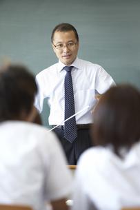 授業をする教師と話を聞く生徒の写真素材 [FYI04067766]