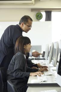 パソコンの授業を受ける女子学生と先生の写真素材 [FYI04067777]