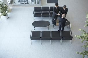 ロビーで名刺を交わしている3人のビジネスマンの写真素材 [FYI04067794]