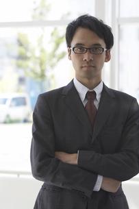 社内で腕を組んで立つ男性社員の写真素材 [FYI04067798]