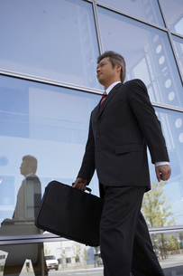 ビルの外を歩くビジネスマンの写真素材 [FYI04067810]