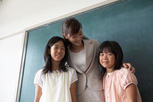 黒板の前に立つ生徒と女性教師の写真素材 [FYI04067826]