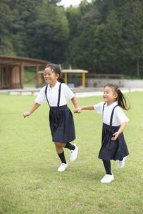 芝生の校庭を走る小学生の姉妹の写真素材 [FYI04067850]