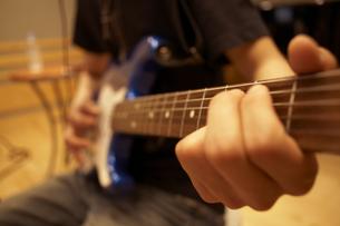 録音スタジオでギターを弾く男性の写真素材 [FYI04067963]