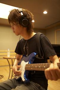 録音スタジオでギターを弾く男性の写真素材 [FYI04067966]