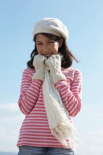 手袋とマフラーをして寒そうにする女の子と青空の写真素材 [FYI04068069]
