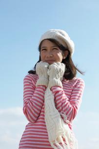 手袋とマフラーをして寒そうにする女の子と青空の写真素材 [FYI04068070]